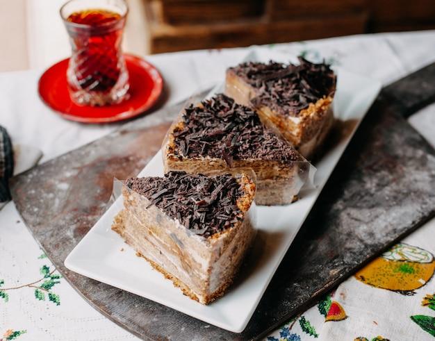 Geschnittener brauner kuchen leckere köstliche schoko-pulver in weißen teller zusammen mit heißem tee