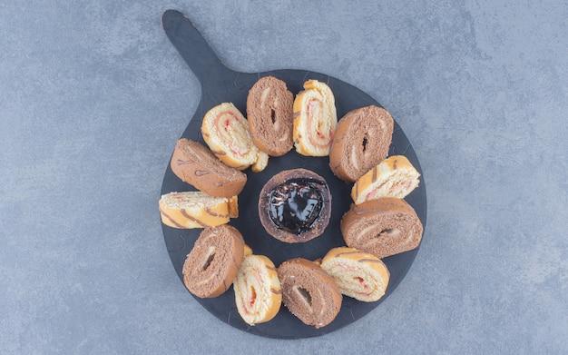 Geschnittener brötchenkuchen auf dem brett, auf dem marmorhintergrund.