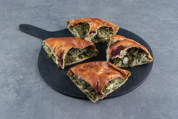 Geschnittener frischer kuchen mit grüns auf schwarzem schneidebrett.