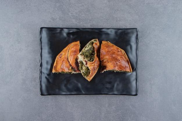 Geschnittener frischer kuchen mit grüns auf schwarzem teller.
