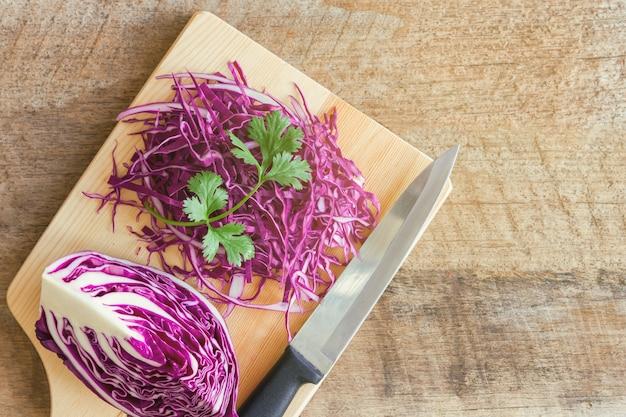 Geschnittener frischer purpurroter oder rotkohl auf hölzernem schneidebrett verzieren mit koriander