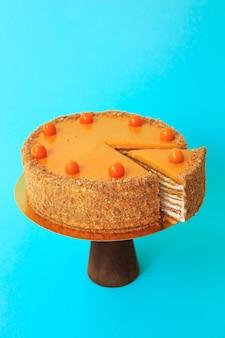 Geschnittener geburtstagskuchen auf dem hölzernen kuchenstand. schöner biskuitkuchen verziert mit physalis mit schlagsahne. blauer hintergrund. platz kopieren. food-fotografie für rezept.