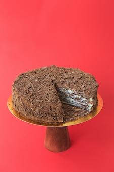 Geschnittener geburtstagskuchen auf dem hölzernen kuchenstand. schöner schokoladen-napoleon-kuchen. roter hintergrund. platz kopieren. food-fotografie für rezept.