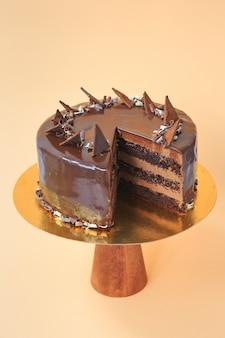 Geschnittener geburtstagskuchen auf dem hölzernen kuchenstand. schöner schokoladenbiskuitkuchen mit schlagsahne. gelber hintergrund. platz kopieren. food-fotografie für rezept.