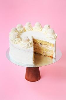 Geschnittener geburtstagskuchen auf dem hölzernen kuchenstand. schöner weißer biskuitkuchen mit schlagsahne. rosa hintergrund. platz kopieren. food-fotografie für rezept.