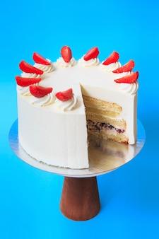 Geschnittener geburtstagskuchen auf dem hölzernen kuchenstand. schöner weißer biskuitkuchen mit schlagsahne und erdbeere. blauer hintergrund. platz kopieren. food-fotografie für rezept.