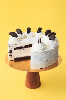 Geschnittener geburtstagskuchen auf dem hölzernen kuchenstand. schöner weißer kuchen mit schlagsahne, verziert mit schwarzen schokoladenkeksen. gelber hintergrund. platz kopieren. food-fotografie für rezept.