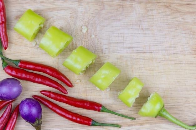 Geschnittener grüner peper, roter peper und aubergine auf einem alten hölzernen brett.