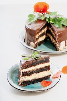 Geschnittener hausgemachter schokoladenkuchen mit erdnussbuttercremeschichten, verziert mit mohnblumen und blütenblättern über einem weißen schreibtisch. selektiver fokus.