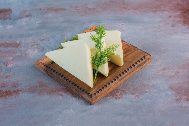 Geschnittener käse und dill auf einem brett nah oben, auf dem marmorhintergrund.