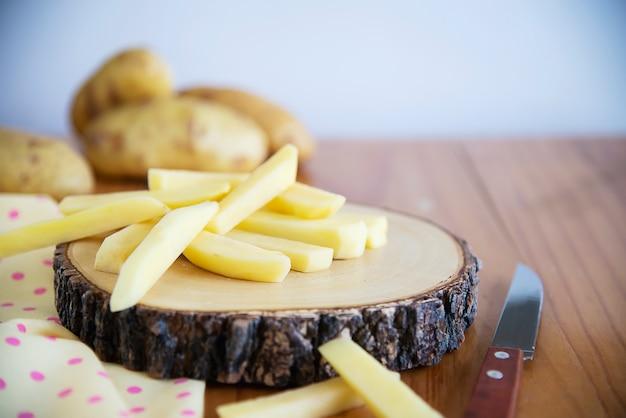 Geschnittener kartoffelstock bereit zur herstellung von pommes-frites - traditionelles lebensmittelzubereitungskonzept
