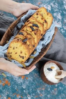 Geschnittener kuchen auf blauem tuch auf hölzernem korb.