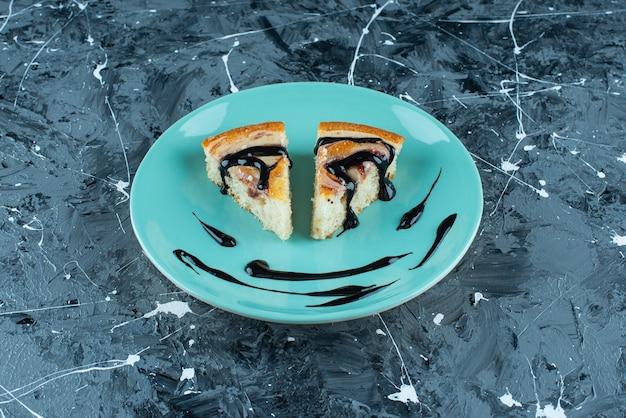 Geschnittener kuchen auf teller, auf dem blauen tisch.
