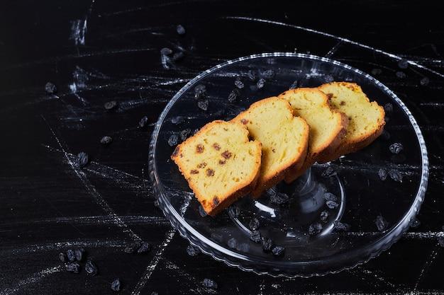 Geschnittener kuchen in einer platte auf schwarz