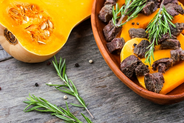 Geschnittener kürbis backte mit fleisch in einem tongefäß. herbstmahlzeit mit rosmarin und gewürzen