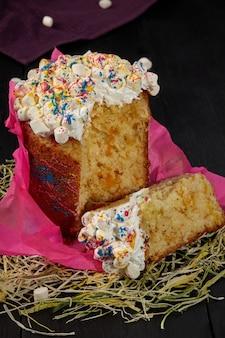 Geschnittener osterkuchen mit geschlagenem eiweiß und marshmallows