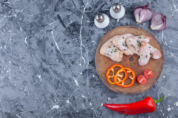 Geschnittener paprika, tomaten und flügel auf einem brett neben zwiebel, salz und pfeffer auf der blauen oberfläche