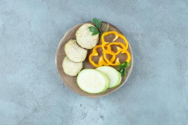 Geschnittener pfeffer, aubergine und zucchini auf keramikplatte.