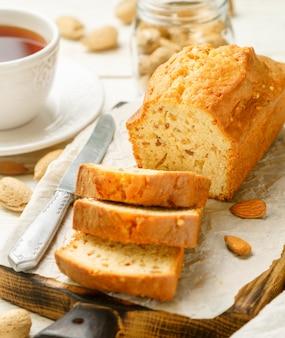 Geschnittener pfundkuchen mit mandeln auf dem schneidebrett. selbst gemachter kuchen mit nüssen und honig
