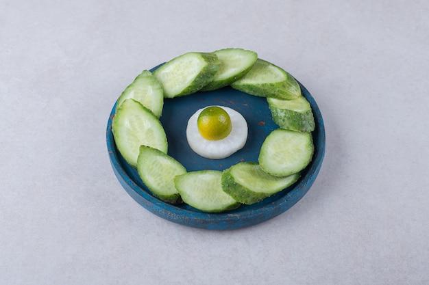 Geschnittener rettich mit kumquat neben geschnittener gurke auf holzplatte auf marmortisch.