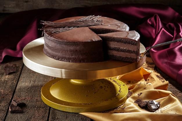 Geschnittener schokoladenbiskuitkuchen mit schokoladenbuttercreme und zuckerguss
