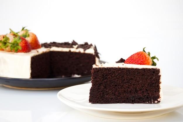 Geschnittener schokoladenkuchen mit schlagsahne, geschnittener schokolade und frischem strawberrie verzieren