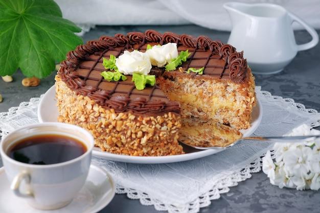 Geschnittener selbst gemachter kiew-kuchen auf der platte und der schale schwarzem kaffee.