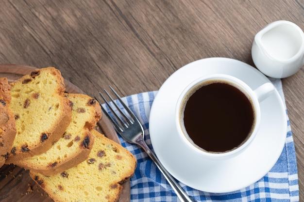 Geschnittener sultaninenkuchen serviert mit einer tasse kaffee.