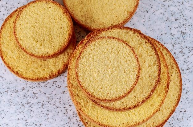 Geschnittener weich- oder biskuitkuchen auf dem tisch zum backen von kuchen.