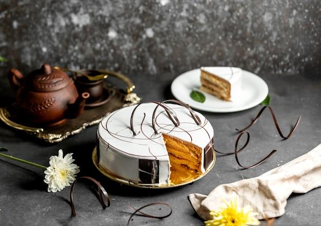 Geschnittener weißer glasierter kuchen, verziert mit schokoladenstücken