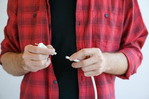Geschnittener weißer kabeldraht des europäischen verlängerungskabels, steckdosenleiste für steckdose an meisterelektrikerhänden, nahaufnahme, reparaturkonzept