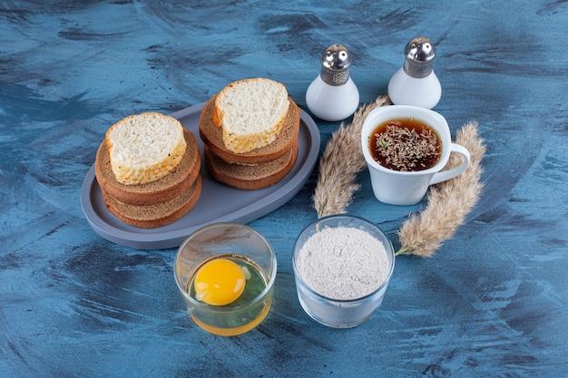 Geschnittenes brot auf einem teller neben ei in einem glas, einer schüssel mehl und einer tasse tee auf dem blauen tisch.