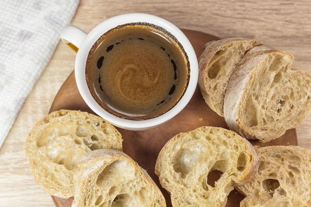 Geschnittenes brot und ein tasse kaffee auf einem hölzernen brett