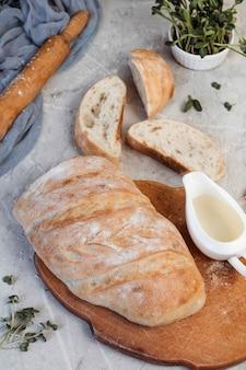 Geschnittenes frisch gebackenes ciabatta-brot auf küchentuch über grauem texturhintergrund.