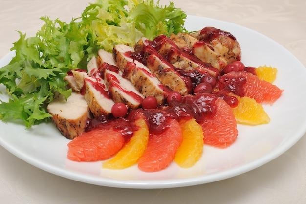 Geschnittenes gebackenes filet mit preiselbeersauce in salatblättern mit orange und grapefruit
