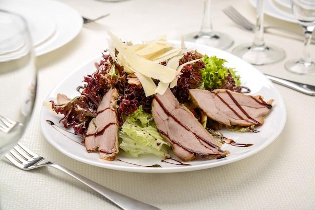 Geschnittenes gegrilltes rindfleischsteak mit grünem blattsalat auf rustikaler platte mit tischbesteck.