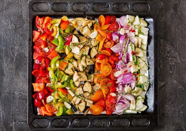 Geschnittenes gemüse auf dem backblech bereitete sich für das backen vor. auberginen, zucchini, tomaten, paprika und zwiebeln. ansicht von oben