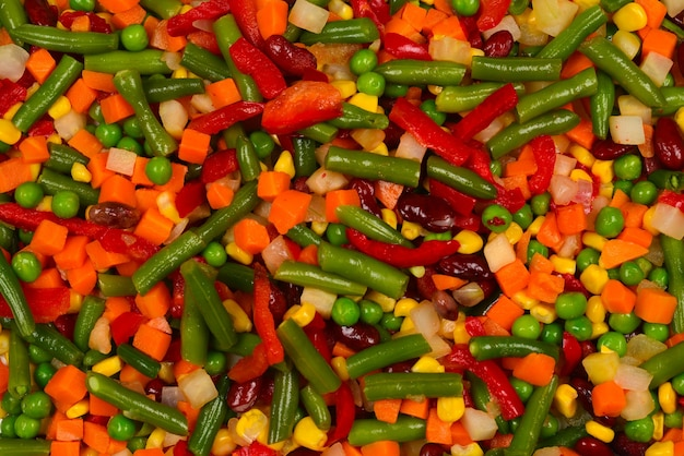 Geschnittenes gemüse, mais, bohnen, erbsen, karotten, paprika hintergrund. Premium Fotos