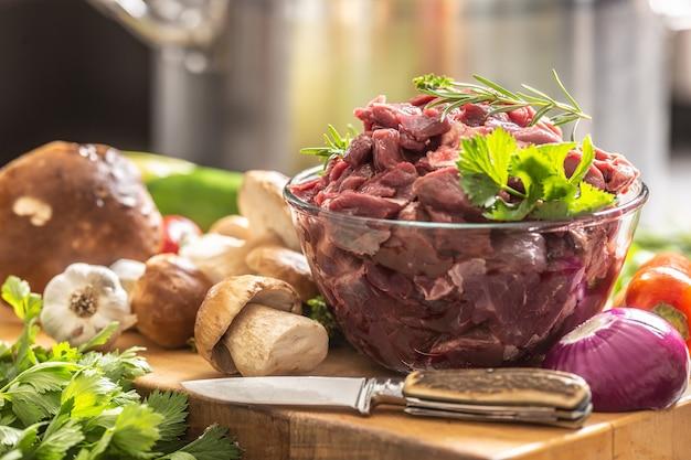 Geschnittenes hirschfleisch zubereitet für eintopf von wild-waldpilzen, kräutern, gemüse und messer.