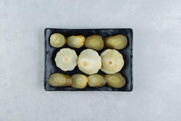 Geschnittenes in essig eingelegtes gemüse auf schwarzem teller.