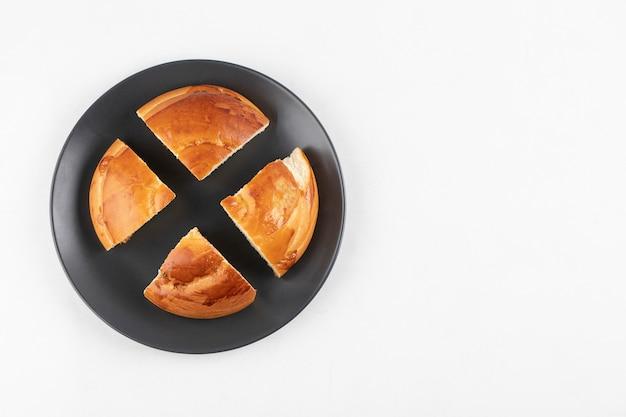 Geschnittenes köstliches frisches gebäck auf schwarzem teller auf weißer oberfläche