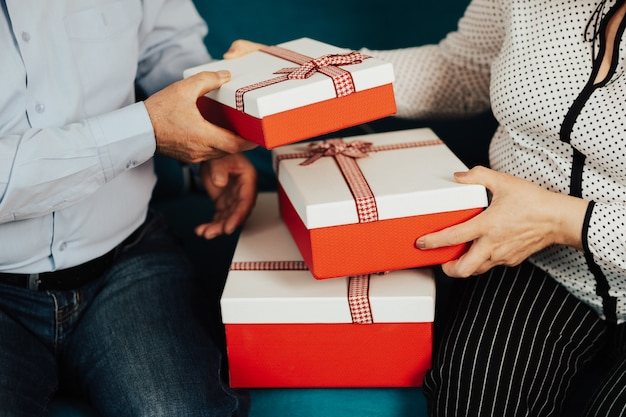Geschnittenes nahaufnahmefoto einer hand des älteren paares hält eine geschenkbox.
