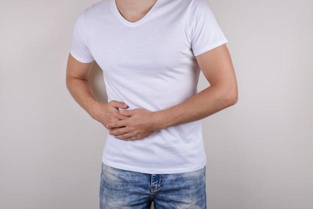 Geschnittenes nahaufnahmefoto-porträt des unglücklichen traurigen verärgerten kerls, der berührende rechte seite hält, die lässige t-shirt-jeanshose isolierte graue wand trägt