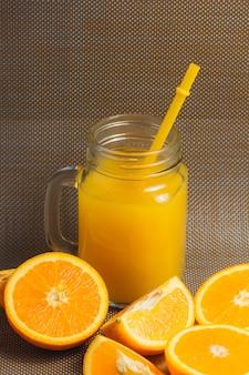 Geschnittenes orangen-und saft-getränk auf dunklem hintergrund