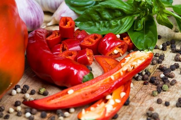Geschnittenes paprika-schneidebrett, auf dem die zutaten für den salat zubereitet werden. geschnittene paprika und andere gewürze in nahaufnahme