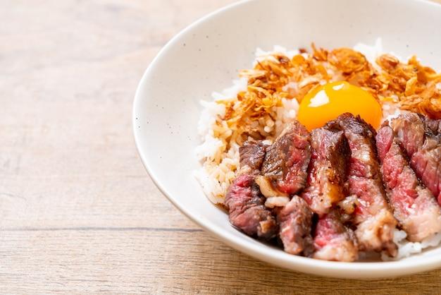 Geschnittenes rindfleisch auf reisschale mit ei nach japanischer art