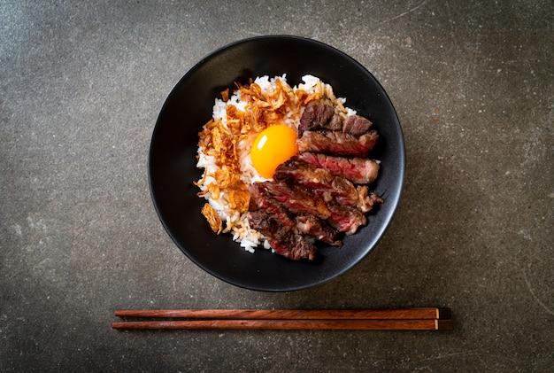 Geschnittenes rindfleisch auf reisschale mit ei Premium Fotos
