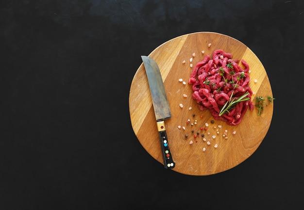 Geschnittenes rohes fleisch auf einem holzbrett. zubereitung von rindfleisch stroganoff.