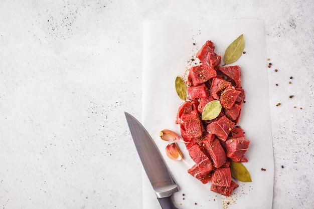 Geschnittenes rohes rindfleisch mit gewürzen auf einem weißen hintergrund, draufsicht.