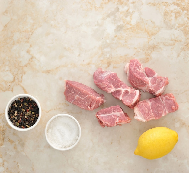 Geschnittenes rohes schweinefleisch und salz, limon und pfeffer